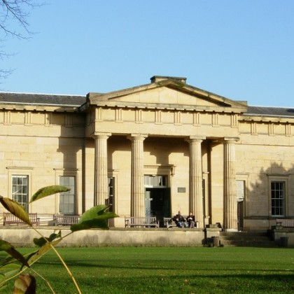 Large building with pillars at the entrance with green lawn and blue sky