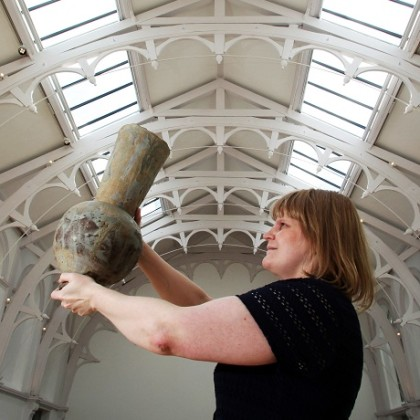 Female curator holds large grey ceramic vessel overhead with Victorian roof space in background