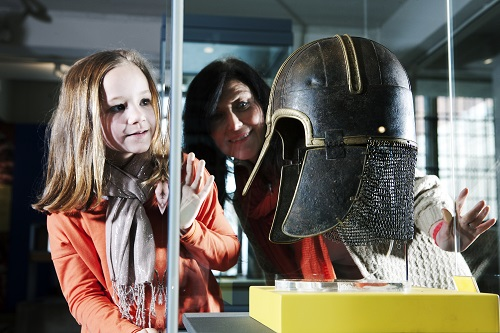 A young girl and woman look at the York Helmet on display
