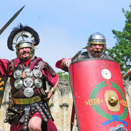 Four men dressed as Roman soldiers, all striking different poses.
