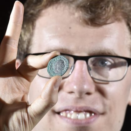 York Museums Trust's curator of numismatics Dr Andrew Woods with one of the coins from the Wold Newton Hoard (image © Anthony Chappel-Ross)