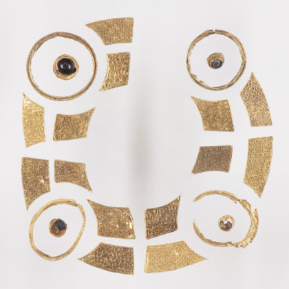 Gold objects of different shapes and sizes which have been laid out in a circle.