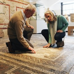 Older man and woman kneel to look at a Roman mosaic floor at the Yorkshire Museum