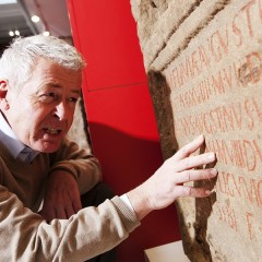 Older man touches relief on Roman stone carved panel at the Yorkshire Museum