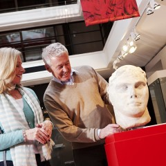 Older man and woman look at a Roman carved head in the Yorkshire Museum
