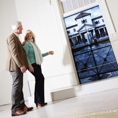 Older man and woman walk towards an interactive screen depicting a Roman-style building at the Yorkshire Museum