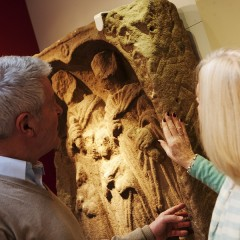 Older man and woman touch Roman stone carving on a wall at the Yorkshire Museum