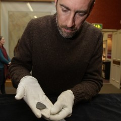 Dr Barry Taylor (University of Chester) with the 11,000 year old engraved shale pendant discovered by archaeologists during excavations at the Early Mesolithic site at Star Carr in North Yorkshire. Image taken at the Yorkshire Museum, York. Credit: Suzy Harrison