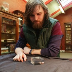 Tom Bell (University of Chester) with the 11,000 year old engraved shale pendant discovered by archaeologists during excavations at the Early Mesolithic site at Star Carr in North Yorkshire. Image taken at the Yorkshire Museum, York. Credit: Suzy Harrison