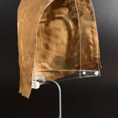 Brown silk cap displayed on clear stand