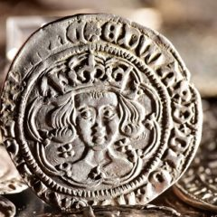 Close-up of silver coin with king's head depicted