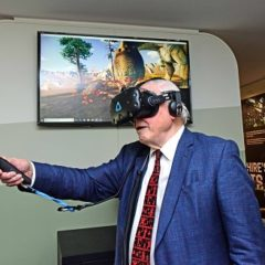 Suited man using a virtual reality head and hand set