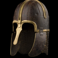 The York Helmet, a medieval helmet made of darkened metal with a gold decoration and nose guard. The helmet has metal plate chin guards and a chainmail neck guard.